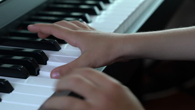Close-up of child playing a piano