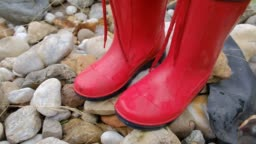 Close-up of child with red rubbert boots