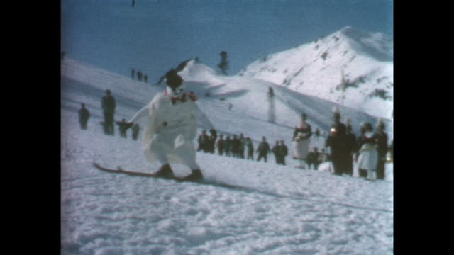 Closeup of clapperboard titled 'Beatle two' stuntman in snowman costume skiing down the mountain and falling in front of the camera shot repeated...