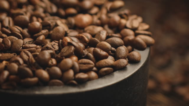 close-up of coffee beans falling in container - coffee drink stock videos & royalty-free footage