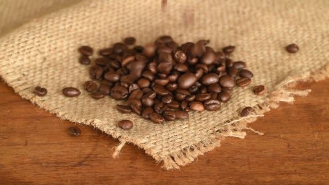 closeup of coffee beans falling on sack - 荒い麻布点の映像素材/bロール