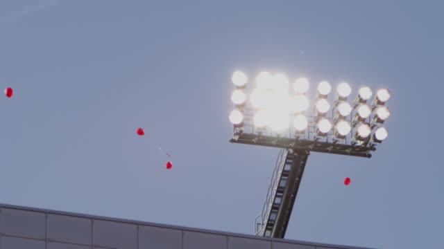 Closeup of collegiate football stadium lights as balloons float to the sky.