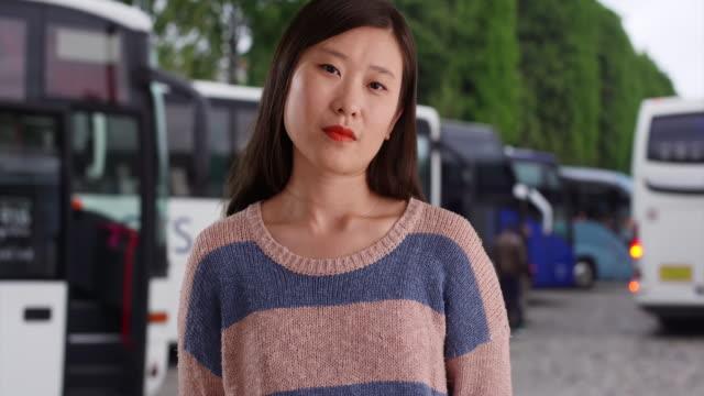vídeos y material grabado en eventos de stock de close-up of confident millennial woman wearing a sweater in front of tour buses - vehículo comercial terrestre