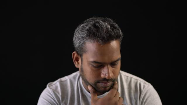 nahaufnahme des verwirrten menschen vor schwarzem hintergrund - einzelner mann über 30 stock-videos und b-roll-filmmaterial
