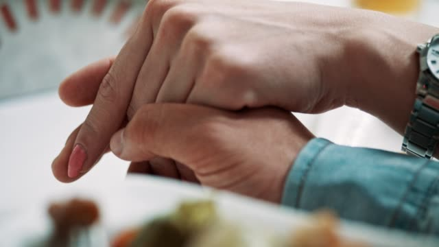 close-up of couple holding hands over table - falling in love stock videos and b-roll footage