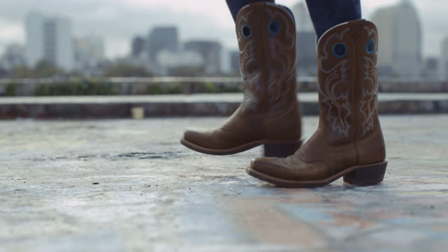 vídeos y material grabado en eventos de stock de close-up of cowboy boots dancing overlooking austin, texas city skyline - vaqueros