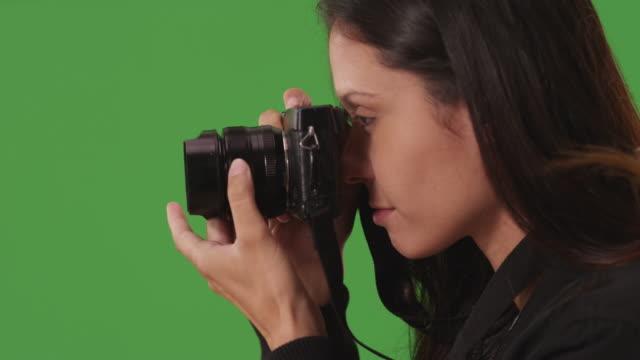 close-up of creative woman using camera to capture images in front green screen - デジタル一眼レフカメラ点の映像素材/bロール