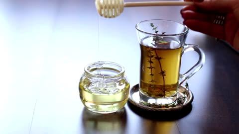 vídeos y material grabado en eventos de stock de primer plano de una taza de té con la miel - miel