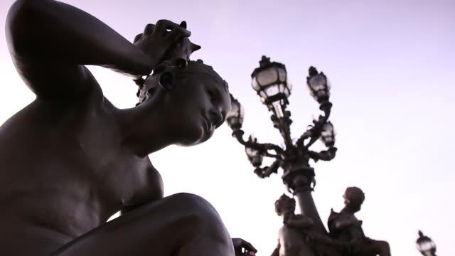 vídeos de stock, filmes e b-roll de close-up of cupid and sea monsters statues on pont alexander iii, paris, france - cupido