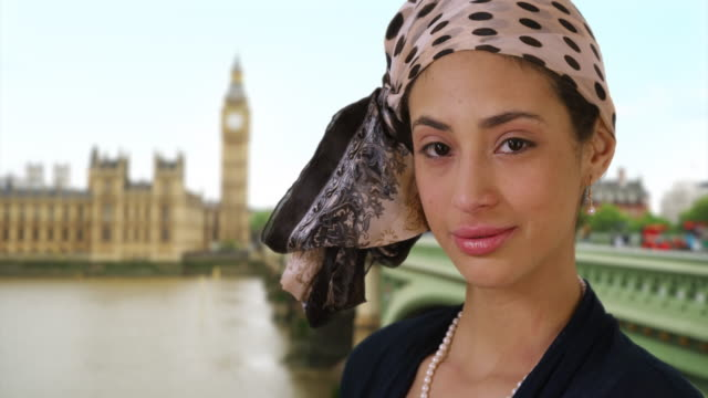 close-up of cute latina woman in stylish headscarf smiling near big ben. - big ben点の映像素材/bロール