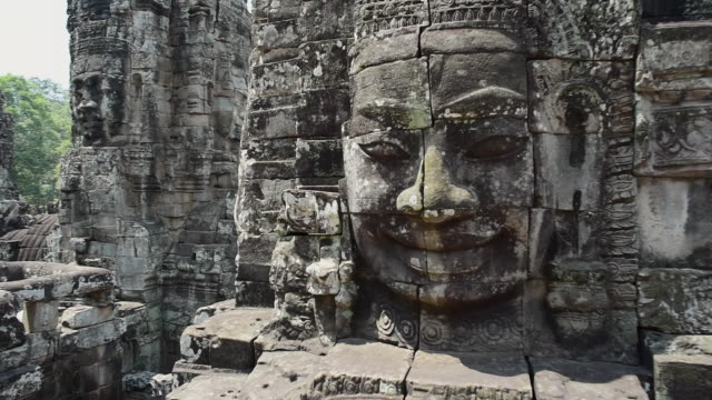 close-up of damaged face sculptures on structures at ancient temple during sunny day - siem reap, cambodia - damaged stock videos & royalty-free footage