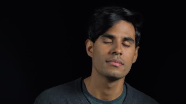 男は黒い背景に対してダンスのクローズ アップ - 目を閉じた点の映像素材/bロール