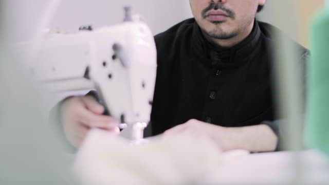 closeup of designer sewing a garment with an industrial sewing machine - industrial designer stock videos & royalty-free footage