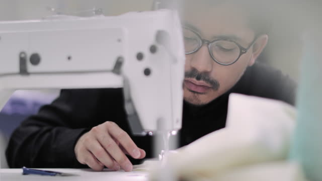 closeup of designer stitching with an industrial sewing machine - industrial designer stock videos & royalty-free footage