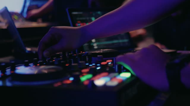 Close-up of DJ hands mixes the track on stage in night club at party