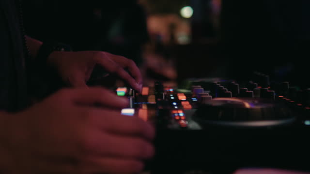 close-up of dj hands mixes the track on stage in night club at party - synthesizer stock videos & royalty-free footage