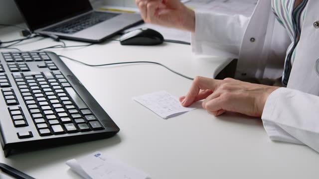 vídeos de stock, filmes e b-roll de close-up de médico fazendo anotações durante chamada de telemedicina - clínica médica