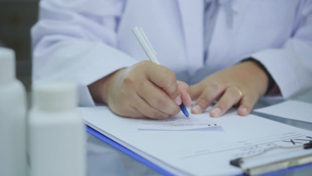 close-up of doctor writing a prescription at desk,slow motion - part of stock videos & royalty-free footage