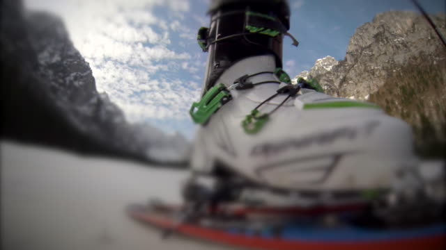 Close-up of downhill skiing boots. - Slow Motion
