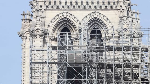 closeup of east facade of cathedral with scaffolding tower / a fire broke out on monday afternoon and quickly spread across the building causing the... - spire stock videos and b-roll footage