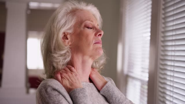 close-up of elder woman with chronic neck pain looking out window worried - pain stock videos & royalty-free footage