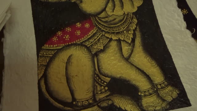 vídeos de stock e filmes b-roll de close-up of elephant painting on paper for sale at store - luang phabang, laos - museu