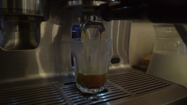 Close-up of espresso pouring from coffee machine. Professional coffee brewing