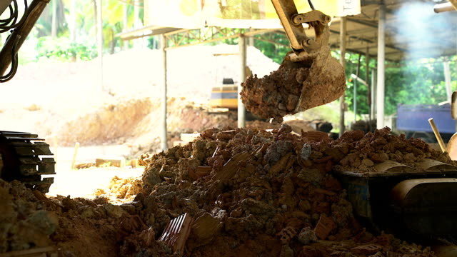 close-up of excavator bucket loading rocks, stones, earth and concrete bricks from demolition site.shot with 4k resolution. - rebuilding stock videos and b-roll footage