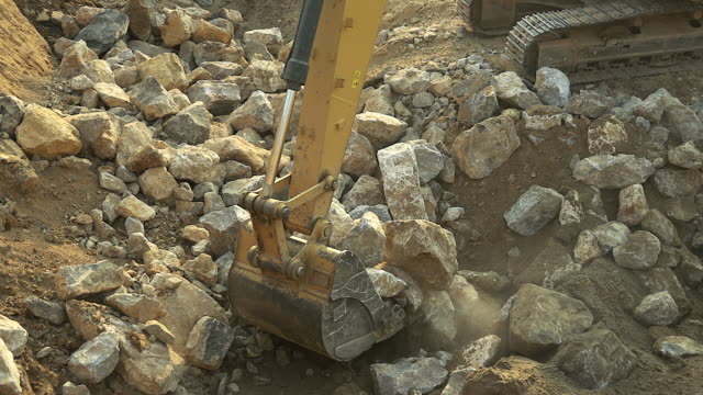 close-up of excavator bucket loading rocks, stones, earth and concrete bricks from demolition site. - earth mover stock videos & royalty-free footage