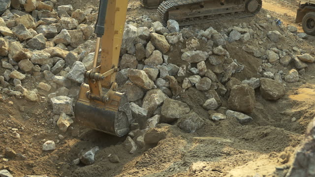 close-up of excavator bucket loading rocks, stones, earth and concrete bricks from demolition site. - hydraulic platform stock videos & royalty-free footage