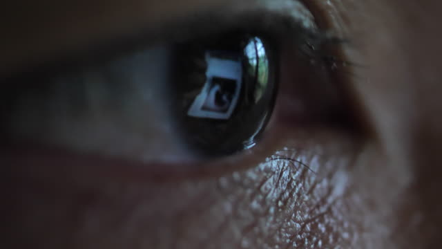 close-up of eye looking on computer monitor and smart phone - guardare in una direzione video stock e b–roll