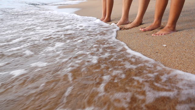 closeup of family legs standing with flowing water on the beach, slow motion - splashing droplet stock videos & royalty-free footage