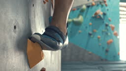 Close-Up Of Feet shod in shoes for rock climbing overcome obstacles on the climbing wall,Slow motion