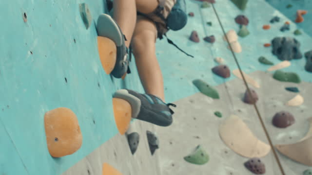 stockvideo's en b-roll-footage met close-up van voeten die in schoenen voor rots het beklimmen worden overwonnen hindernissen op de het beklimmen muur, langzame motie - boulder