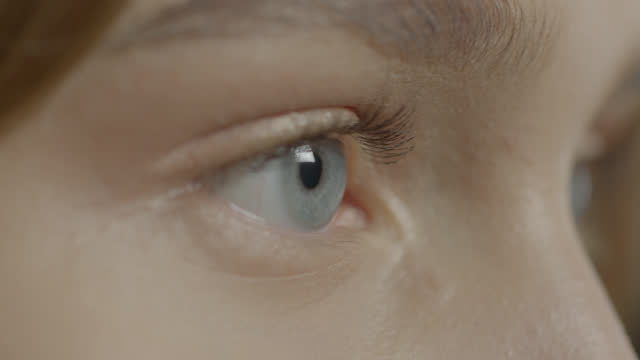 close-up of female blue eyes. - blue eyes stock videos & royalty-free footage