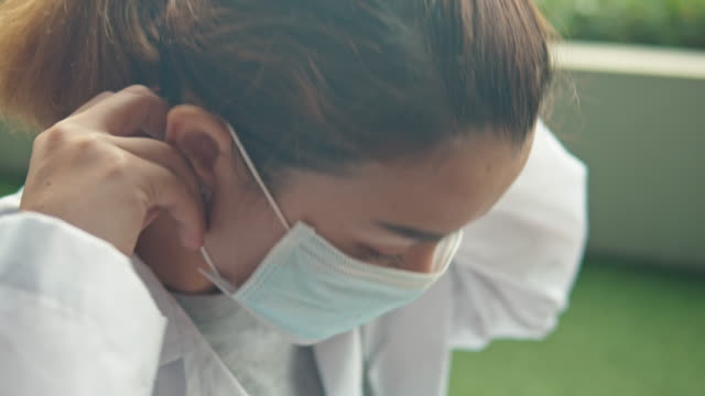 close-up of female doctor wearing surgical mask to protect corona virus(covid-19),tilt up - protective workwear stock videos & royalty-free footage