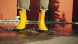 Close-up of female feet in bright rubber boots jumping in puddle outdoors