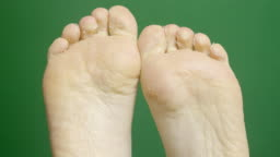 Close-up of female foots during dermatology treatment SPA procedures on the green chroma-key backdrop.
