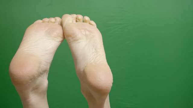 close-up of female foots during dermatology treatment spa procedures on the green chroma-key backdrop. - barefoot stock videos & royalty-free footage