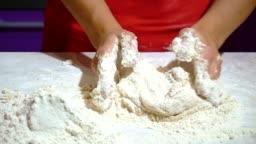Close-up of female hands preparing pizza dough.