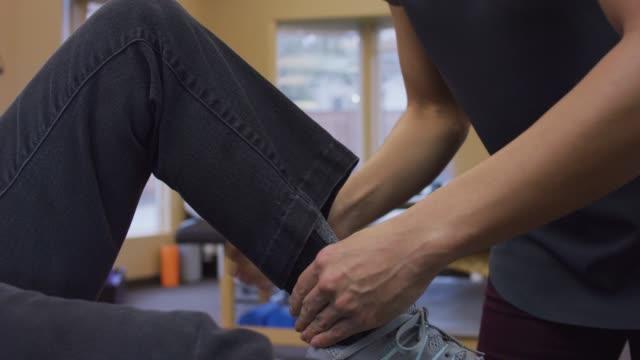 vídeos y material grabado en eventos de stock de primer plano de mujer fisioterapeuta manos masaje músculo de la pantorrilla femenina mayores - fisioterapia deportiva