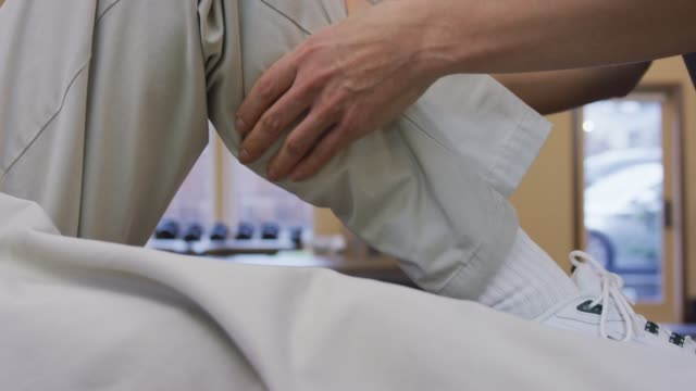 Closeup of Female Physical Therapist's Hands Massaging Male Calf Muscle