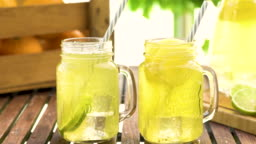 Close-up of filling fresh lemonade in mason jar glass on wooden table outside