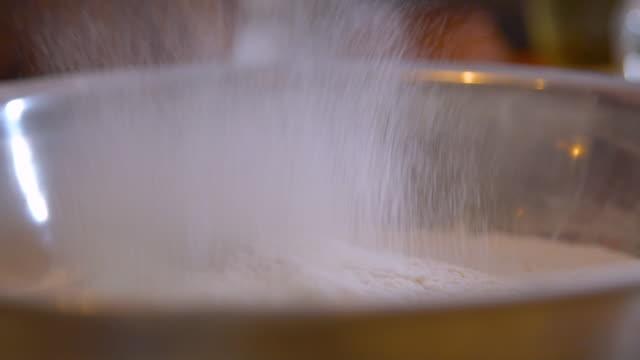vídeos de stock, filmes e b-roll de close-up da farinha através de uma briga da peneira do metal no fundo do borrão da natureza. ingredientes e estágios de preparação - sprinkles