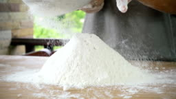 Close-up of flour through a metal sieve fray in nature blur background. Ingredients and preparation stages. Slowmotion shot