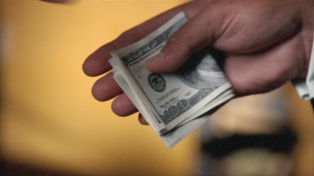 close-up of folded us$100 bills exchanging hands between two men - giving stock videos and b-roll footage