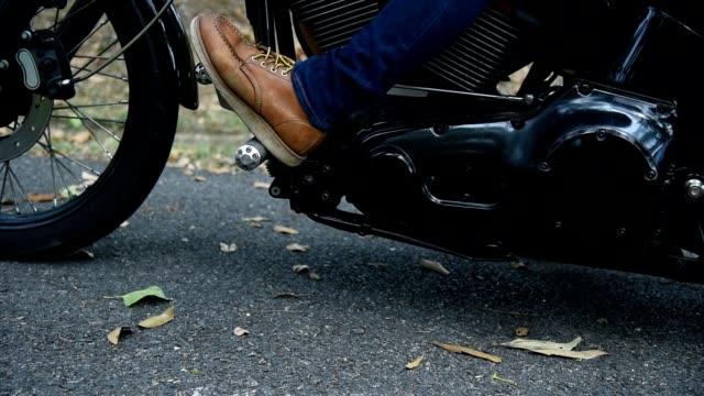 nahaufnahme der fußfrau in stiefeln auf einem motorrad. - motorradfahrer stock-videos und b-roll-filmmaterial