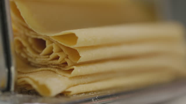 close-up of fresh pasta sheets folding from pasta machine - man and machine stock videos & royalty-free footage