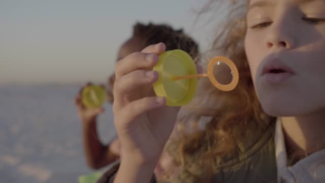 close-up of girl and boy blowing bubbles at beach on windy day - bubble wand stock videos & royalty-free footage
