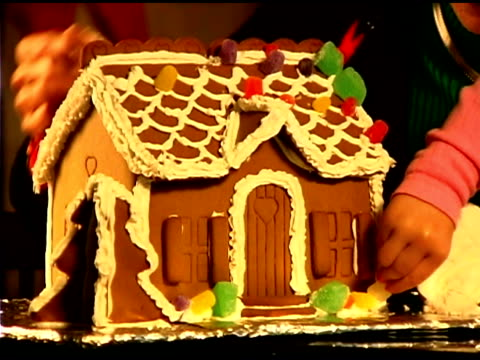 close-up of girl and grandmother decorating gingerbread house - see other clips from this shoot 1407 stock videos and b-roll footage